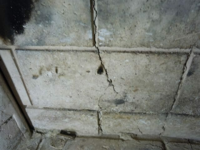Manufactured fireplace often have refractory (concrete like) panels in them for limiting the transfer of heat in the firebox area. Fires can occur in a few instances if the cracks allow excessive heat to transfer through them.