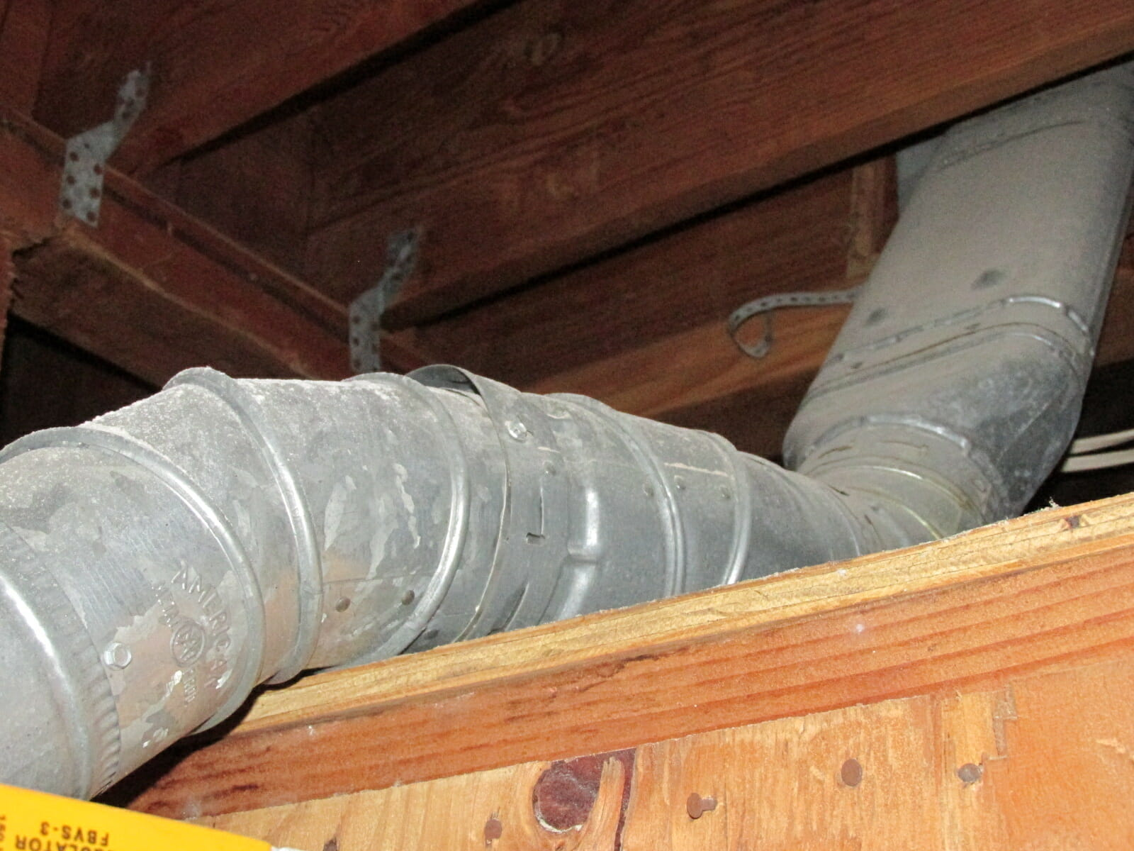 Water heater vent against wood
