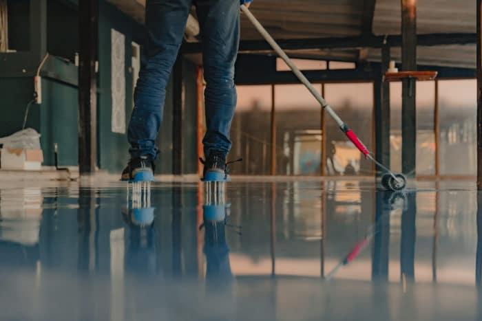 Applyihg gray epoxy resin to a concrete floor